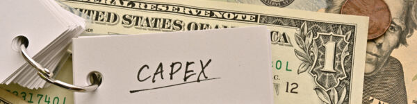 An image of American dollars on a table top. Sitting on top of the dollars is a keyring of small white cards, which is open to show the word 'CAPEX'.