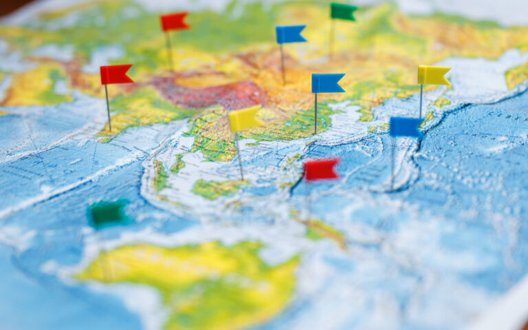 An image of a part of the world map. Red and blue flags are stick into it in various locations.