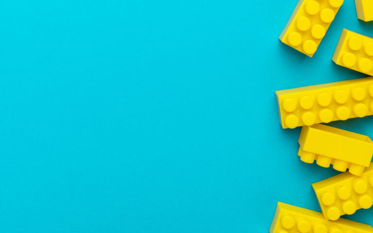 An image of yellow lego bricks scattered on the right hand side of a bright blue background.